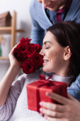 Usmívající se žena vonící růže, zatímco manžel drží dárek na rozmazané popředí