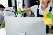 Lächelnde Reinigungskraft hält Lappen und Waschmittel in der Nähe des Computermonitors im Büro