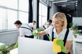 Reinigungskraft lächelt beim Putzen des Computermonitors mit Waschmittel im Büro