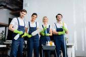 Multietničtí pracovníci úklidové služby s úsměvem na kameru v kanceláři