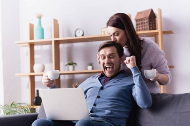 Excited man with cup looking at laptop near wife stock vector