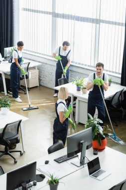 High angle view of multiethnic cleaners washing floor near computers in office stock vector