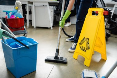Cropped view of cleaner using vacuum cleaner near wet floor signboard in office stock vector