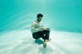 Arabský podnikatel používající notebook pod vodou v bazénu
