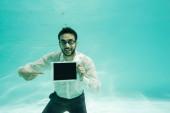Arab üzletember mosolyog és mutat a digitális tabletta üres képernyő víz alatt