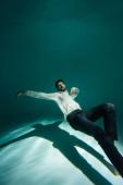 Arabský podnikatel v bílé košili plavání v bazénu