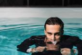 Muslimischer Geschäftsmann blickt in Schwimmbad in Kamera