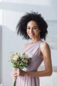 elegante afrikanisch-amerikanische Brautjungfer lächelt in die Kamera, während sie den Hochzeitsstrauß hält