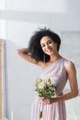 charmante afrikanisch-amerikanische Brautjungfer berührt Haare, während sie Brautstrauß hält