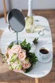 Hochzeitsstrauß, Spiegel und Kaffeetasse in der Nähe der Champagnerflasche auf verschwommenem Hintergrund