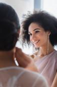 šťastný africký americký žena dívá na nevěsta na rozmazané popředí