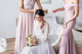 boldog menyasszony ül esküvői csokor, míg koszorúslányok rögzíti a fátylat