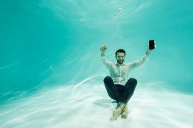 Cheerful arabian businessman with smartphone showing yes gesture underwater stock vector