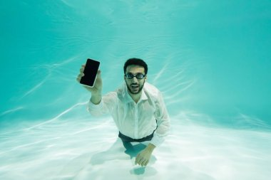 Positive arabian businessman showing smartphone with blank screen in swimming pool stock vector
