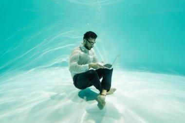 Arabian businessman using laptop underwater in pool stock vector