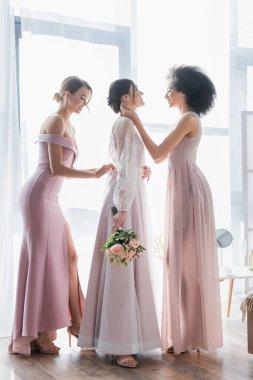 Side view of interracial bridesmaids preparing bride for wedding stock vector