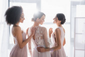 young multiethnic bridesmaids standing near charming bride in sunshine at home