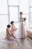 multikulturní družičky upravující šaty půvabné nevěsty v ložnici