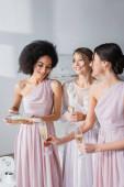 Afrikai amerikai nő pezsgőt önt a boldog menyasszony és koszorúslány poharába.