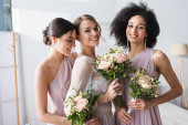 pretty bride together with interracial bridesmaids holding wedding bouquets in bedroom