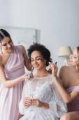 usmívající se družičky nanášející řasenku a pudr na africkou americkou nevěstu