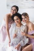 glückliche Brautjungfern lächeln in die Kamera, während sie Champagner in der Nähe der afrikanisch-amerikanischen Braut halten