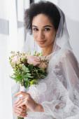 csinos afro-amerikai menyasszony kezében esküvői csokor, miközben nézi a kamera