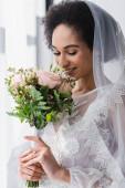 mosolygó afro-amerikai menyasszony élvezi illata esküvői csokor