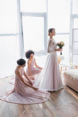 Multicultural bridesmaids adjusting dress of charming bride in bedroom stock vector