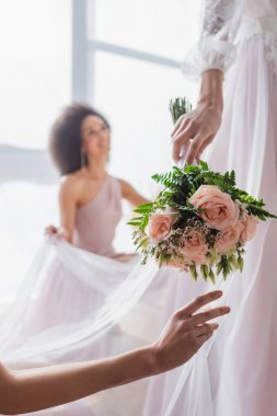 Selective focus of wedding bouquet in hand of bride near african american bridesmaid on blurred background stock vector