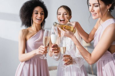 Young woman pouring champagne near african american friend and bride on blurred background stock vector