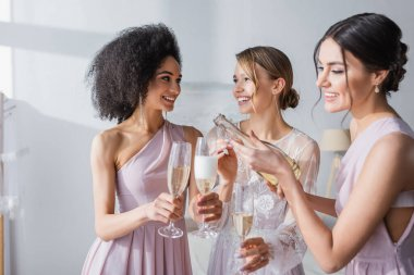 Smiling woman pouring champagne near happy bride and african american bridesmaid stock vector
