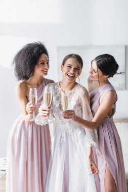 Laughing bride holding champagne near cheerful interracial friends in bedroom stock vector