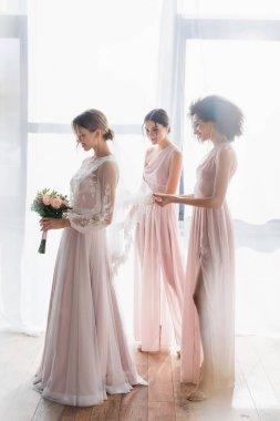 Full length view of multiethnic bridesmaids near elegant bride holding wedding bouquet stock vector