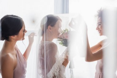 Side view of happy interracial bridesmaids near smiling bride in veil on blurred foreground stock vector