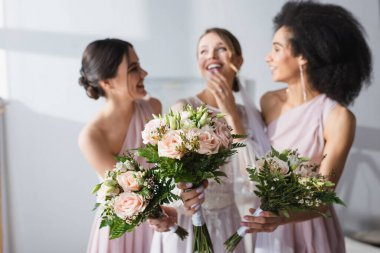 Laughing bride and multicultural bridesmaids holding wedding bouquets on blurred background stock vector
