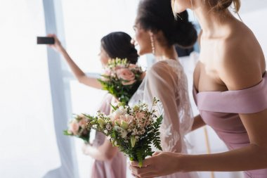 Bride taking selfie with interracial bridesmaids holding wedding bouquets, blurred background stock vector