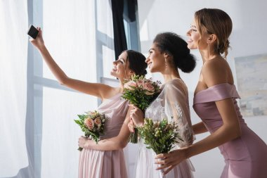 African american bride with bridesmaids holding wedding bouquets while taking selfie on smartphone stock vector