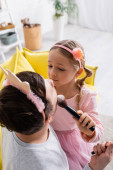 high angle view of girl in toy crown doing makeup to father on blurred foreground