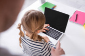 magas szög kilátás lány közelében laptop és apa ujjal mutogató homályos előtérben