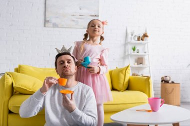 dad and daughter holding toy cups while playing prince and princess at home