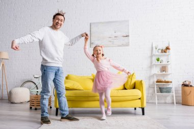 happy father and daughter in toy crowns smiling at camera while dancing in living room
