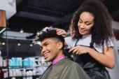 Lächelnde afrikanisch-amerikanische Friseurin im Schürzenschnitt Hals der Kundin im Salon