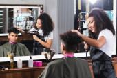 Afrikai amerikai fodrász szárító haj a fiatal férfi elmosódott előtérben tükör közelében szalonban