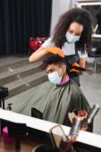 Afrikai amerikai férfi orvosi maszkban ül közelében fodrász trimmer