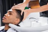 Kadeřník mytí hlavy afrického amerického klienta v blízkosti dřezu v salonu