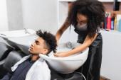 Afroamerikanischer Friseur wäscht Haare eines Mannes in Handtuch