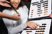 Cropped view of african american hairdresser touching hair of client pointing at color swatches in salon