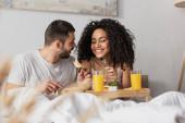 veselý mezirasový pár jíst snídani v posteli