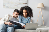 interracial couple looking at laptop in bedroom